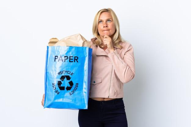 疑問と思考を持って白で隔離のリサイクルする紙でいっぱいのリサイクルバッグを保持している中年女性