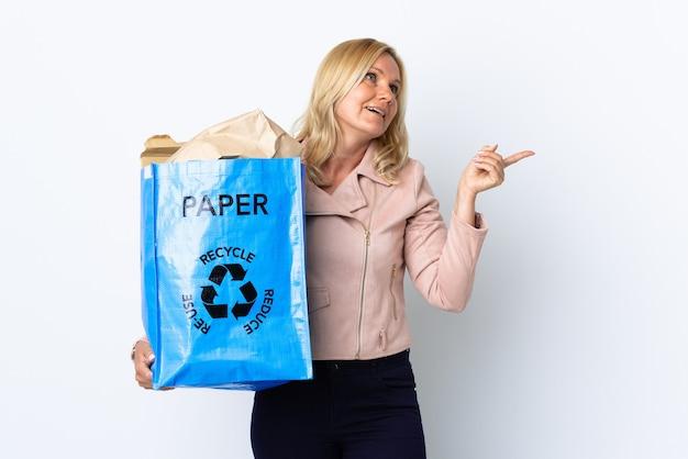 指を持ち上げながら解決策を実現することを意図して白で隔離リサイクルする紙でいっぱいのリサイクルバッグを保持している中年女性