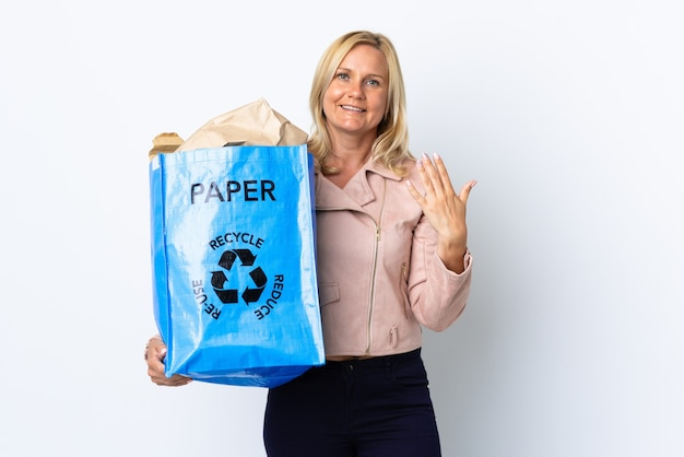 手に持って来るように誘う白で隔離されたリサイクルする紙でいっぱいのリサイクルバッグを持っている中年女性。あなたが来て幸せ