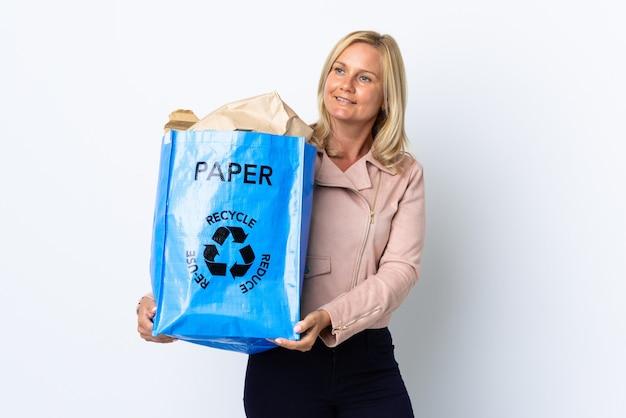 紙でいっぱいのリサイクルバッグを持ってリサイクルする中年女性は、横を見て笑って白で隔離