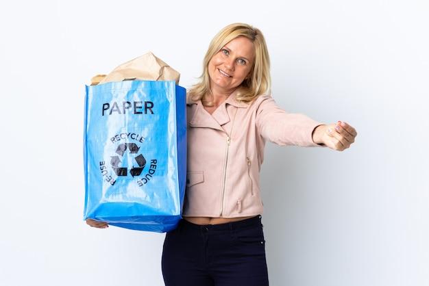 白で隔離されたリサイクルするために紙でいっぱいのリサイクルバッグを持っている中年の女性はお金を稼ぐジェスチャー