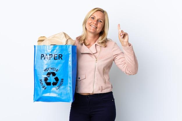 紙でいっぱいのリサイクルバッグを持っている中年の女性は、素晴らしいアイデアを指している白で隔離されたリサイクルする