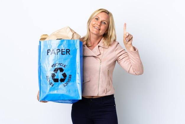 紙でいっぱいのリサイクルバッグを持ってリサイクルする中年の女性は、最高の兆候を示して指を持ち上げて白で隔離