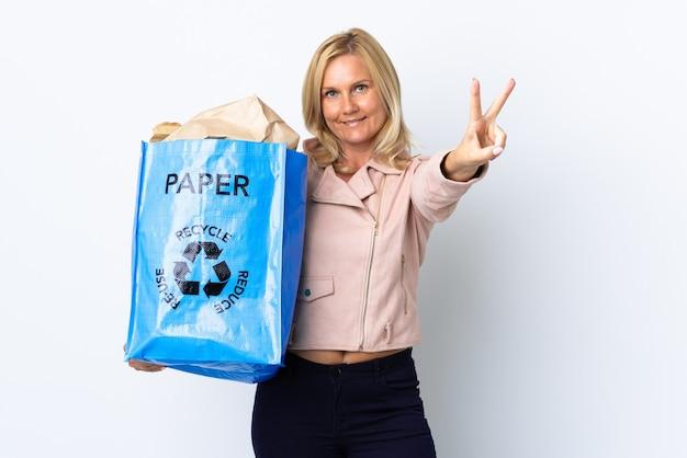 紙でいっぱいのリサイクルバッグを持っている中年の女性は、白い笑顔と勝利のサインを示して分離されたリサイクルする