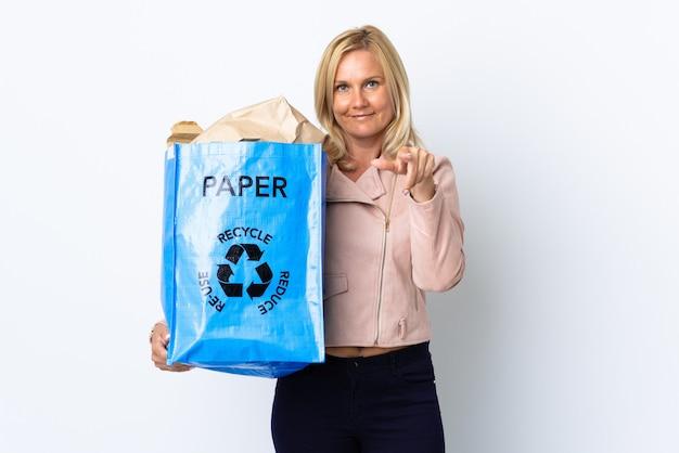 紙でいっぱいのリサイクルバッグを持っている中年女性が驚いて正面を向いて白で隔離されたリサイクル