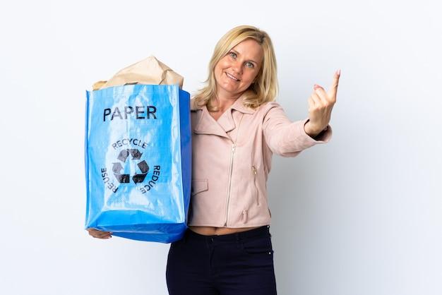 Женщина среднего возраста, держащая мешок для переработки, полный бумаги для переработки, изолирована на белой стене, делая приближающийся жест