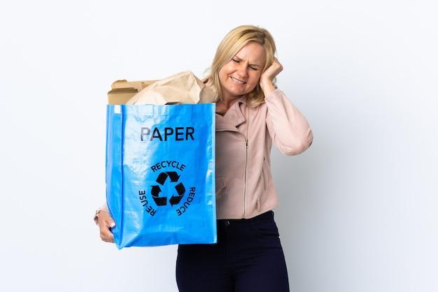 欲求不満と耳を覆う白い壁に隔離されたリサイクルする紙でいっぱいのリサイクルバッグを保持している中年の女性