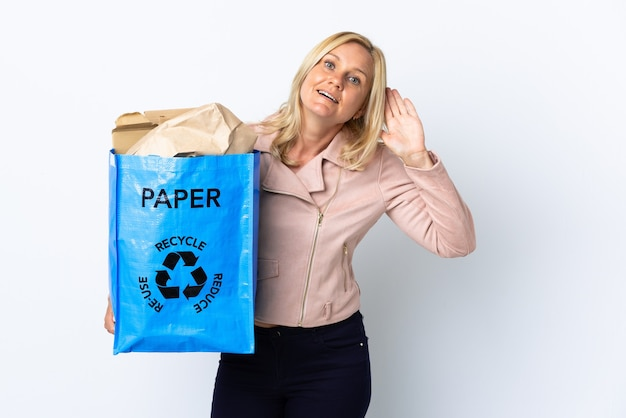 耳に手を置いて何かを聞いて白い壁に隔離されたリサイクルする紙でいっぱいのリサイクルバッグを持っている中年女性