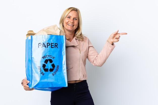 白い壁に隔離されたリサイクル用の紙でいっぱいのリサイクルバッグを持っている中年女性は、指を横に向けて製品を提示します