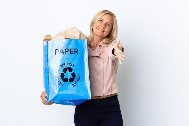 좋은 거래를 닫기 위해 악수하는 흰 벽에 고립 된 재활용 종이의 전체 재활용 가방을 들고 중년 여성