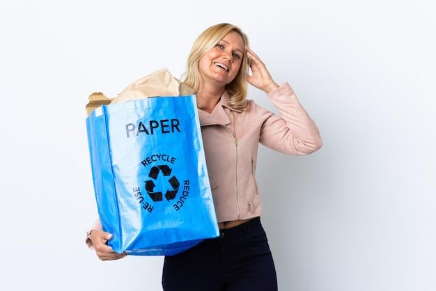 たくさん笑って白い壁に隔離されたリサイクルする紙でいっぱいのリサイクルバッグを保持している中年女性