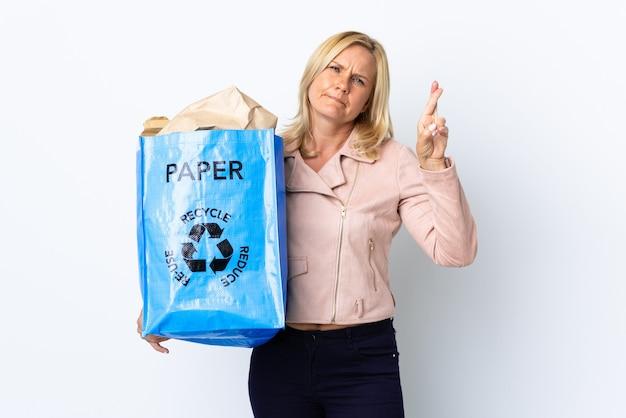 紙でいっぱいのリサイクルバッグを持っている中年の女性は、指を交差させて、最高の願いを白で隔離してリサイクルします