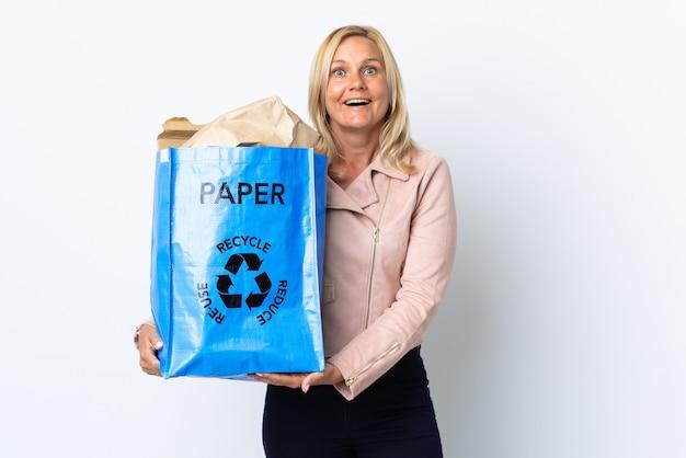 驚きの表情で白で隔離のリサイクルする紙でいっぱいのリサイクルバッグを保持している中年女性