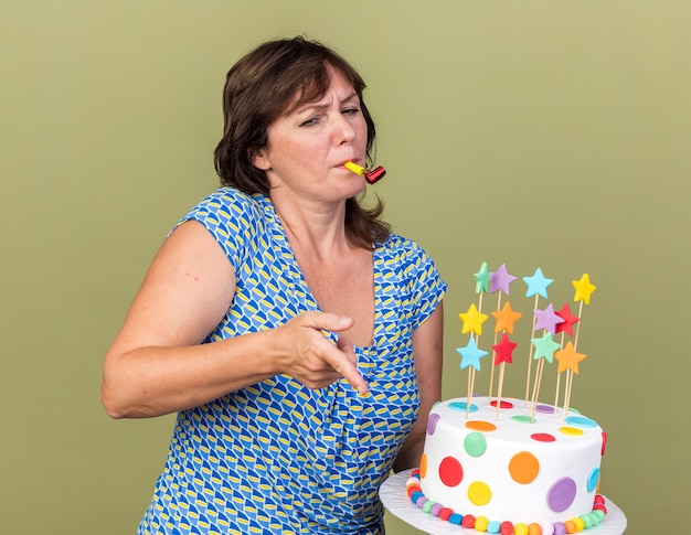 Middle age woman holding birthday cake blowing whistle pointing with index finger at something looking confised celebrating birthday party standing over green wall