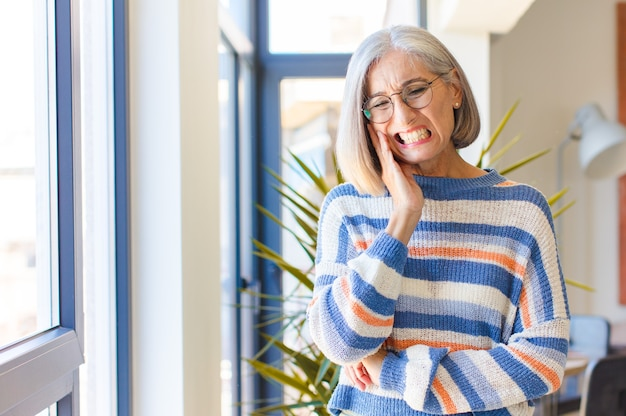 Женщина среднего возраста держится за щеку и страдает от болезненной зубной боли, чувствует себя больной, несчастной и несчастной, ищет стоматолога