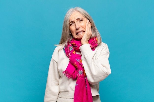 Middle age woman holding cheek and suffering painful toothache, feeling ill, miserable and unhappy, looking for a dentist