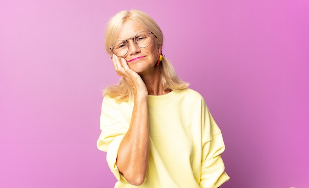 Middle age woman holding cheek and suffering painful toothache isolated