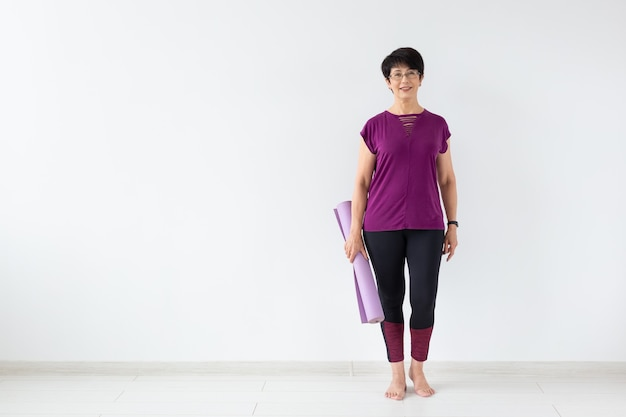 Middle age woman holding mat after a yoga class