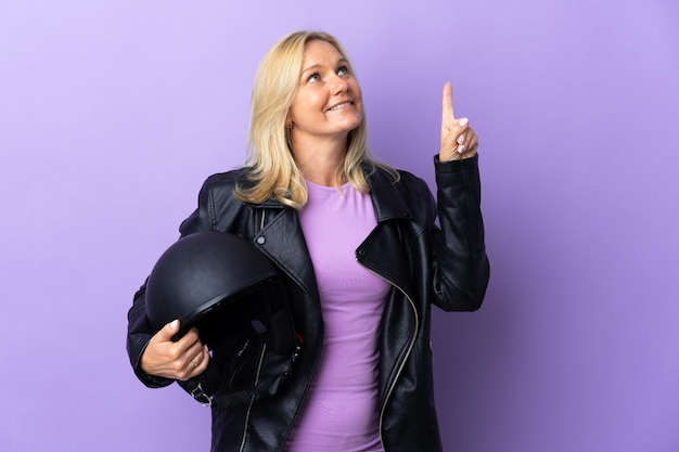 Middle age woman holding a motorcycle helmet isolated on purple pointing up a great idea