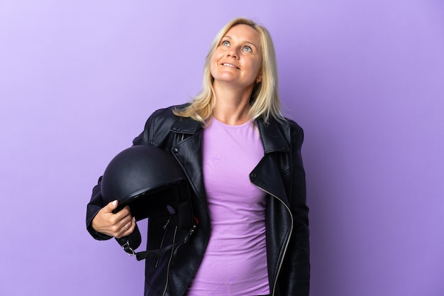 Middle age woman holding a motorcycle helmet isolated on purple thinking an idea while looking up