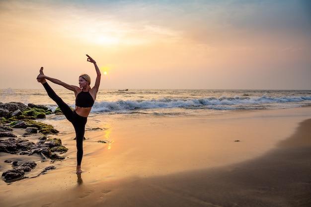 모래 해변에 검은 요가 중년 여성