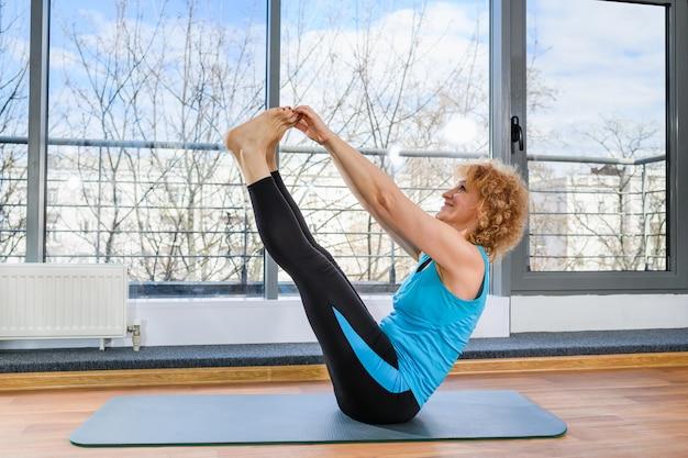Женщина среднего возраста в синей спортивной одежде сидит на коврике и держит руками пальцы ног, упражнения йоги и фитнеса