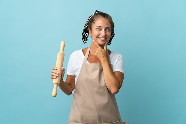 横を向いて笑っているシェフの制服を着た中年女性