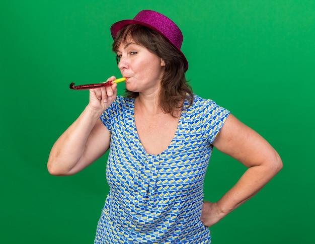 幸せで陽気な笛を吹くパーティーハットの中年女性