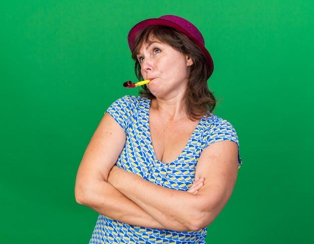 困惑して見上げる笛を吹くパーティーハットの中年女性