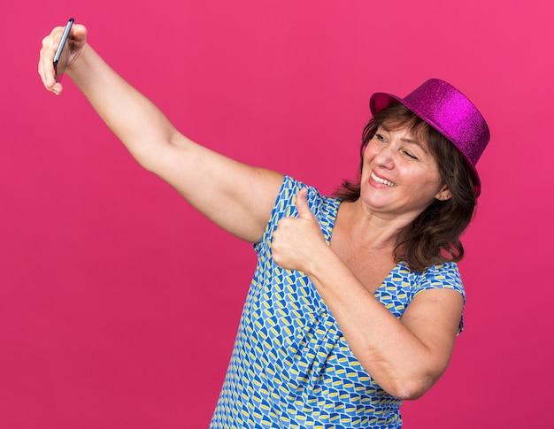 スマートフォンを使用して自分撮りをしているパーティーハットの中年女性は、親指を立てて幸せで陽気な笑顔を見せています