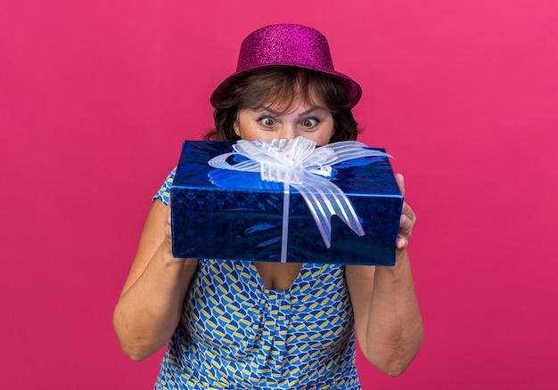 Женщина среднего возраста в праздничной шляпе с подарком, глядя на него, заинтриговала празднование дня рождения, стоя над розовой стеной