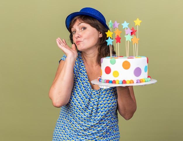 Женщина среднего возраста в праздничной шляпе держит праздничный торт, глядя в сторону с застенчивой улыбкой на лице, празднует день рождения, стоя над зеленой стеной