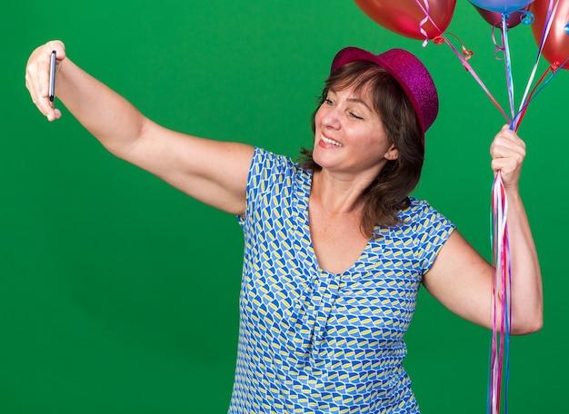녹색 벽 위에 서 행복하고 쾌활한 축하 생일 파티 스마트 폰을 사용하여 셀카를하고 다채로운 풍선을 들고 파티 모자에 중년 여자