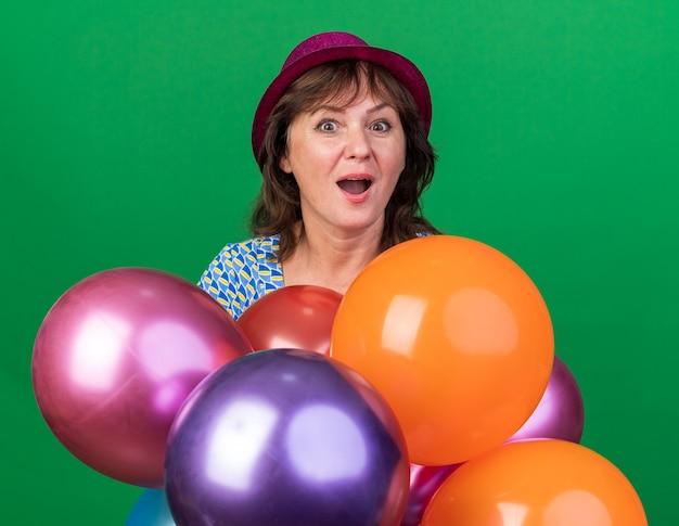 다채로운 풍선을 들고 파티 모자에 중년 여자 행복하고 흥분 녹색 벽 위에 서있는 생일 파티를 축하 웃고