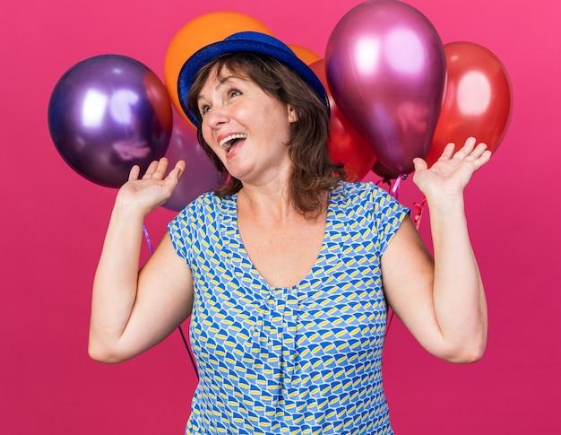 Женщина среднего возраста в партийной шляпе держит разноцветные воздушные шары, счастливая и взволнованная, весело улыбаясь
