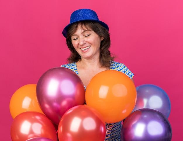 カラフルな風船を持っているパーティーハットの中年女性は元気に笑顔で幸せで興奮しています