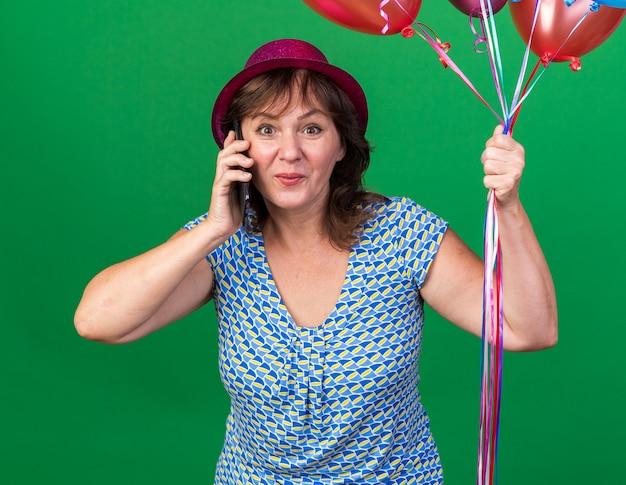 Женщина среднего возраста в партийной шляпе с разноцветными воздушными шарами выглядит счастливой и удивленной, разговаривая по мобильному телефону, празднуя день рождения, стоя над зеленой стеной