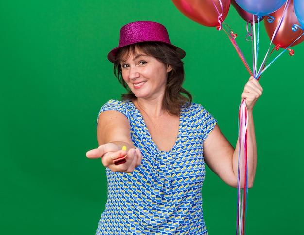 Женщина среднего возраста в праздничной шляпе держит разноцветные воздушные шары, протягивая свисток с улыбкой на лице, празднует день рождения, стоя над зеленой стеной