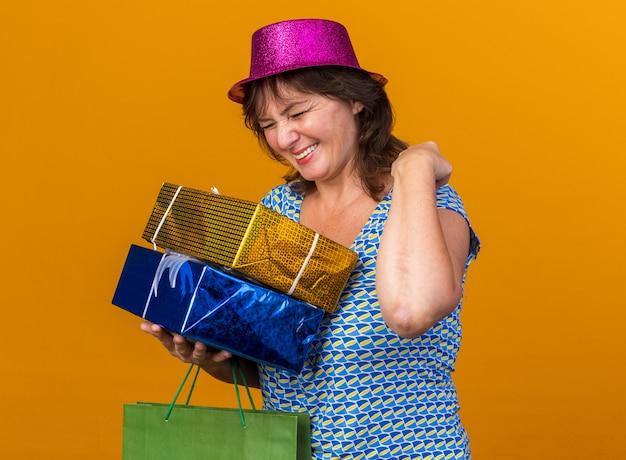 Женщина средних лет в праздничной шляпе держит бумажный пакет с подарками на день рождения, счастливая и взволнованная, сжимая кулак, празднует день рождения, стоя над оранжевой стеной