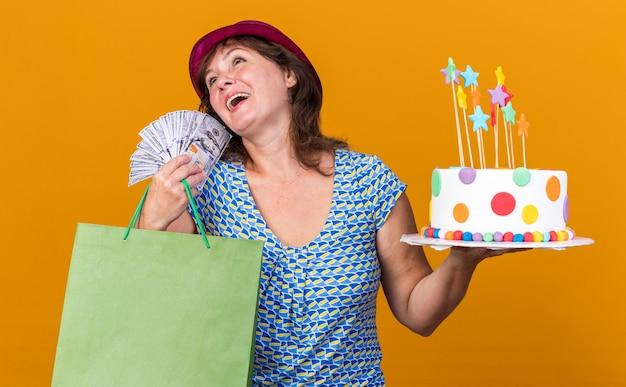 생일 케이크와 현금을 들고 선물로 종이 가방을 들고 파티 모자에 중년 여성이 행복하고 오렌지 벽 위에 서있는 생일 파티를 축하하는 유쾌하게 웃고 기쁘게 생각합니다.