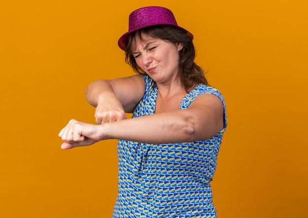 Женщина среднего возраста в партийной шляпе выглядит смущенной и недовольной, сжимая кулаки, празднует день рождения, стоя над оранжевой стеной