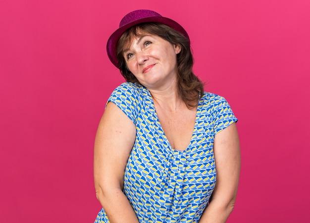 분홍색 벽 위에 서 행복하고 쾌활한 축하 생일 파티를 찾고 파티 모자에 중년 여자