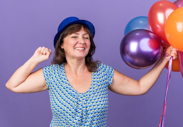 보라색 벽 위에 서 행복하고 흥분 축하 생일 파티 주먹을 떨림 다채로운 풍선의 무리와 함께 파티 모자에 중년 여자