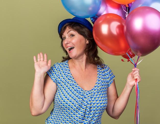 Женщина среднего возраста в партийной шляпе с кучей разноцветных шаров счастлива и взволнована, весело улыбаясь с поднятой рукой, празднуя день рождения, стоя над зеленой стеной