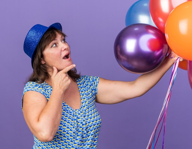 그들을보고 다채로운 풍선의 무리와 함께 파티 모자에 중년 여자 보라색 벽 위에 서있는 축하 생일 파티를 놀라게하고 놀란