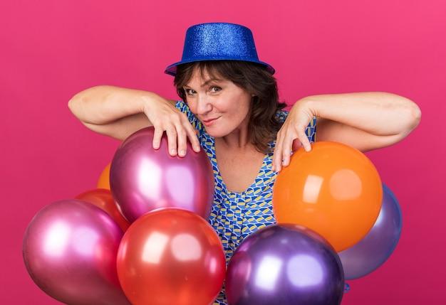 핑크 벽 위에 서있는 축하 생일 파티를 축하하는 다채로운 풍선과 함께 파티 모자에 중년 여자 행복하고 즐거운 미소