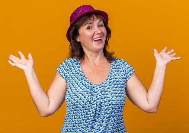 Женщина среднего возраста в партийной шляпе со счастливым лицом улыбается, весело поднимая руки