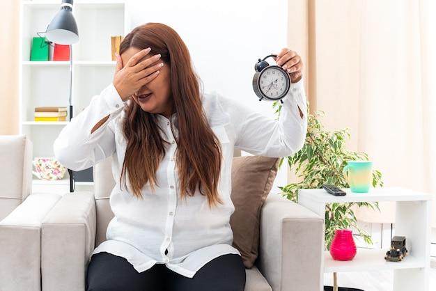 Женщина среднего возраста в белой рубашке и черных штанах держит будильник, закрывающий глаза, рука сидит на стуле в светлой гостиной