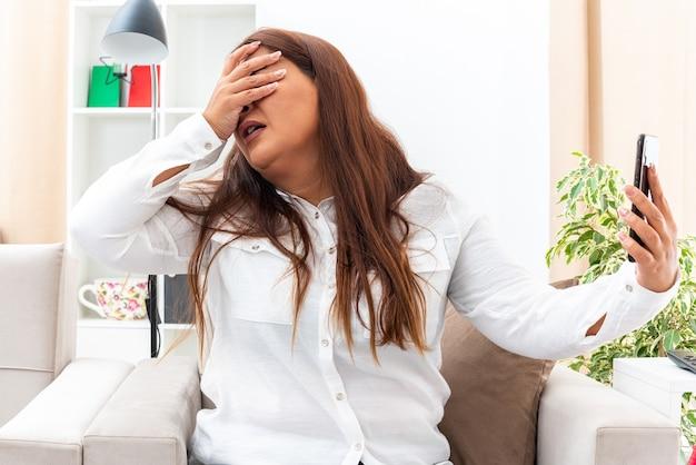 白いシャツと黒いズボンを着た中年の女性がスマートフォンを持ち、明るいリビングルームの椅子に座ってイライラしてイライラしているように見える