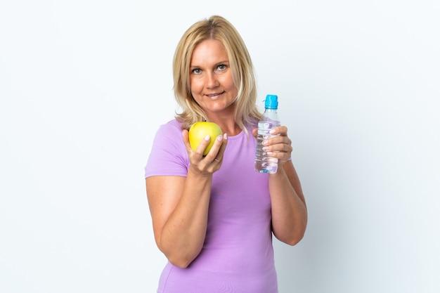 リンゴと水のボトルで白い壁に隔離された中年女性